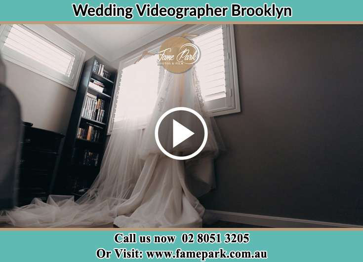 Bride wedding gown hang at the window Brooklyn NSW 2083