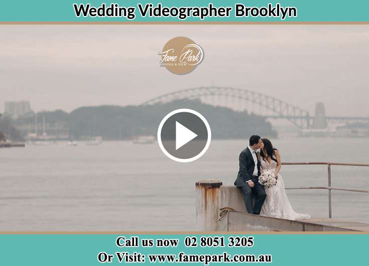 Bride and Groom kissed while sitting on near the shore Brooklyn NSW 2083